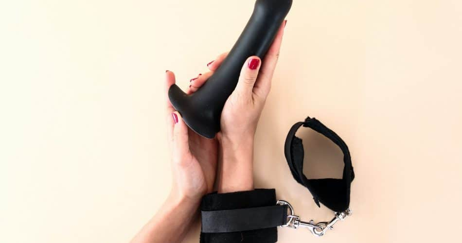 hands-with-handcuffs-holding-phallic-object