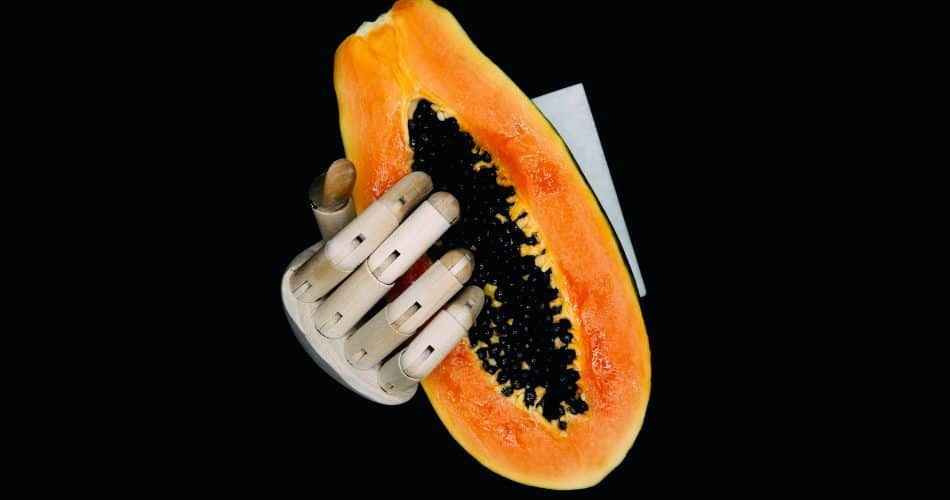wooden-fingers-papaya-seeds-black-background
